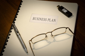 Business Plan on a desk wiht a pen, a thumb drive and a pair of glasses
